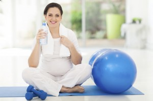 pregnant woman holding bottle of water